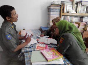 Arief Dwisaputra (kiri) sedang menjelaskan tata kelola perpustakaan yang baik dan benar kepada Kepala MI Cokroaminoto (kanan) dan ketua tim pengembang budaya baca (tengah)