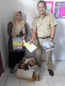 Tunjukkan buku-seorang guru dengan buku - buku yang akan disumbangkan kepada madrasah